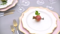 Elegant plates of unusual shape, decorated with pomegranate and cutlery on a wedding banquet table 76390155