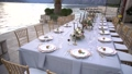 A table at a wedding banquet, decorated with flowers, candlesticks and young pomegranates on the pier in the Bay of Kotor 76390158