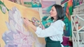 Woman artist working with the big painting at workshop 76408106