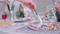 Artist mixes paints on the palette 76408116