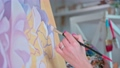 Young woman artist painting picture on canvas in art workshop close up 76408124
