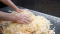 Woman kneads sauerkraut with carrots on the table. Hands of woman cooking video footage 1920x1080 76418276
