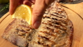 Hand is squeezing slowly a lemon juice on the grilled white Mackerel fish fillet 76419256