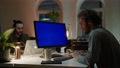 Curly haired guy sits at blue monitor against coworker 76478751