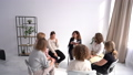 Only women sit in the office in a circle during the master class. A girl tells her colleagues about something by gesturing, another girl writes down 76515815