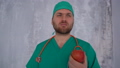 Young doctor in a green medical suit and cap with a phonendoscope on his shoulders eating an apple 76515837