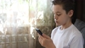 Young boy at home with smartphone 76518600