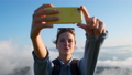happy young woman traveller is taking selfies by smartphone at top of mount 76526095