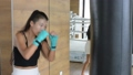 Asian woman kick boxer punching and kicking bag in gym 76546946