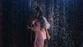 Love story of couple in rain, expressed in passionate dance. Romantic meeting of two lovers. Wet bodies of man and a woman, covered in glistening drops in the soft studio light. Close up. Slow motion. 76584489