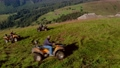 Male tourists riding quad bikes in mountain. 76603424