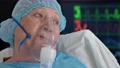 Portrait of old woman in oxygen mask on hospital bed against background of monitor with vital signs 76612174