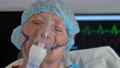 Portrait of old dying woman with closed eyes in oxygen mask on hospital bed 76613210