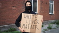 Man in mask stands with cardboard poster in hands - WHITE LIVES MATTER 76630344