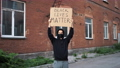 Man in mask stands with cardboard poster in hands - BLACK LIVES MATTER 76630345