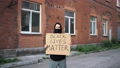 Man in mask stands with cardboard poster in hands - BLACK LIVES MATTER 76630346