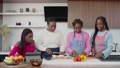 Positive affectionate black mother slicing chicken on cutting board and cute teenage daughters in aprons chopping vegetables on chopping board, while united family preparing lunch together in kitchen. 76647081