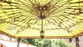 An antique lantern on the ceiling of a wrought-iron gazebo with a yellow roof. 76647783
