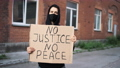 Man in mask stands with cardboard poster in hands - BLACK LIVES MATTER 76665811