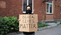 Man in mask stands with cardboard poster in hands - BLACK LIVES MATTER 76665830