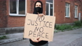 Man in mask stands with cardboard poster in hands - BLACK LIVES MATTER 76665838