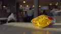 French fries potatoes lie on table inside cafe restaurant, man's hand takes and eats it. Fastfood. Unhealthy lifestyle, fried high calorie harmful food. Visitors in background make order near checkout 76675850