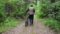 Man walks and rolls a bicycle next to him along a forest path. Bike malfunction, damage, breakdown. View of the cyclist's back. Sport, recreation and pastimes, health benefits, fitness. Trip journey 76675862