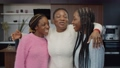 Lifestyle portrait of cheerful lovely african american teenage daughters with stylish haircut bonding and kissing joyful attractive mom, expressing love and happiness while family relaxing at home. 76684117
