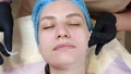 close-up, cosmetician in medical gloves applies evenly cosmetic cream or sunscreen to female face after peeling. skincare and sun protection concept. cosmetology on beauty salon 76690853