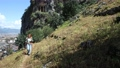 Young European woman walks down hill with hiking poles against backdrop of town of Fethiye in Turkey. 76722881