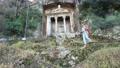 Redhead Caucasian woman walks downhill using trekking poles after visiting Amynthas Rock Tomb in Fethiye, Turkey. 76722883