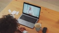 Young african female in self-isolation communicates with a doctor by video call using a laptop, a patient consults a doctor online while in quarantine, coronovirus pandemic. 76738300
