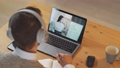 Man student sits at a desk at home and study online using a laptop, student learns in a remote lesson by video call with a asian teacher, education in the conditions of the coronovirus pandemic 76738334