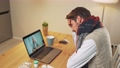 Sick man in self-isolation communicates with a doctor female by video call using a laptop, a patient consults a doctor online while in quarantine, a coronovirus pandemic. 76738338