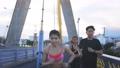 Young man and woman friends running at bridge 76754835