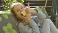 Little child blond girl is eating red apple on a swing outdoor during summer sunny day on playground in the garden, healthy food, happy childhood concept 76757912