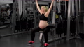 Gym workout Pregnant woman sportswear training shoulders with exercise machine  76771125