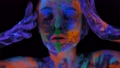 A magical space girl with UV drawings on her face and body in the dark. Body art 76802042