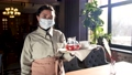 Waitress in mask and with tray standing in cafe 76803110