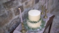 White cream cake, decorated with olive and eucalyptus sprigs, next to the burning candles in golden candlesticks 76803679
