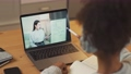 African girl sits at a desk and study online using a laptop, a schoolgirl learns in a remote lesson by video call with a asian teacher, education in the conditions of the coronovirus pandemic 76819779