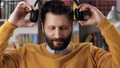 Online learning, remote education, video call, e-learning, remote presentation concept. Positive bearded man looking at camera puts on wireless headphones on his head and then takes off headphones 76833931