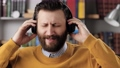 Man with headphones listens to music and sings. Positive bearded man in black wireless headphones holds his head with his hands and sings song while enjoying music. Slow motion 76833939
