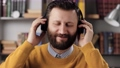 Man with headphones listens to music. Positive bearded man in black wireless headphones holds his head with his hands and enjoys music. Slow motion 76833940