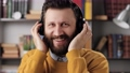 Man with headphones talks and laughs. Positive bearded male teacher or businessman with headphones talking to someone and laughing. Slow motion 76833943