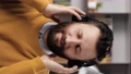 Man with headphones listens to music. Vertical video of positive bearded man in black wireless headphones holds his head with his hands and enjoys music. Slow motion 76833944