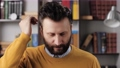 Man combing his hair with his fingers. Bearded man smoothes hair on his head with his hand. Slow motion 76833947