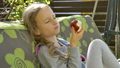 Little child blond girl is eating red apple on a swing outdoor during summer sunny day on playground in the garden, healthy food, happy childhood concept 76842629
