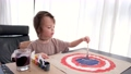 Young boy draws picture on cardboard with gouache at table 76845731