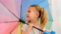 Playful little girl in gray t-shirt poses with open umbrella 76845733